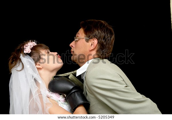 The bride kisses the groom on a black background
