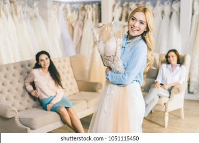 Bride with lace dress and friends in wedding fashion shop