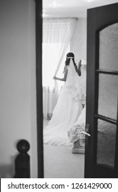 bride in lace dress looks out the window