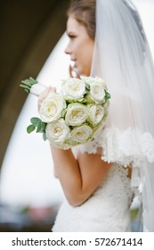 Bride in lace veil holds wedding bouquet made of white roses