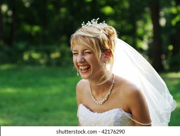 Bride laughing expressively on the meadow during the photo session.
