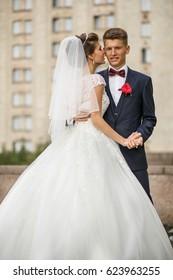 Bride leans to groom tender posing outside