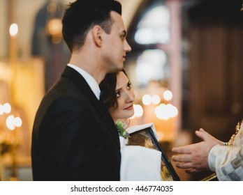 Bride leans to groom's shoulder holding an icon in her arms