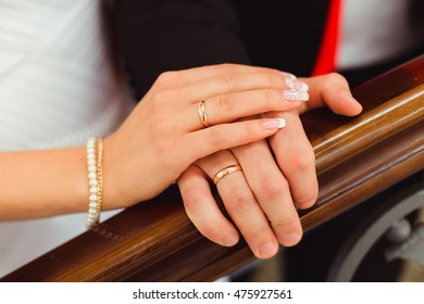 Bride lies her hand over groom's one while standing before wooden handrails