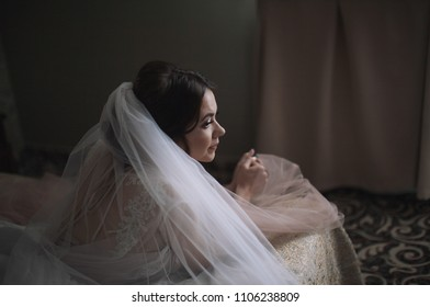 the bride lies on a bed in a hotel in a delicate dress waiting for the groom