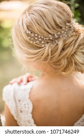 Bride in a light pink dress with an elegant hairdo posing on a summery blurred background