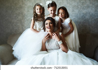Bride and little girls sit on a grey sofa