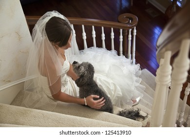 Bride looks lovingly at her dog before her wedding.