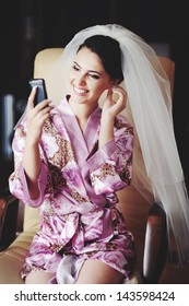 bride looks in to mobile phone using at as a mirror, happy bridal morning