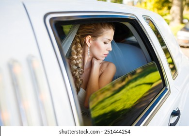 Bride looks out of the window a white limousine