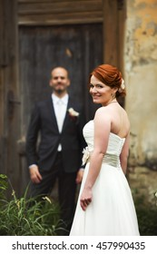 Bride looks over her shoulder while groom waits for her at the old door