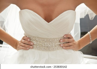 bride in luxury dress with plunging neckline, arms akimbo
