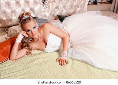 Bride lying on a bed in a wedding dress on their wedding night