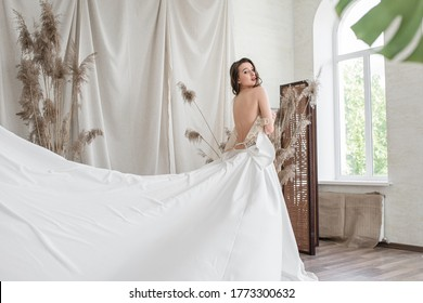 The bride in a magnificent dress. Beautiful girl bride in a magnificent dress. Luxurious bedroom interior