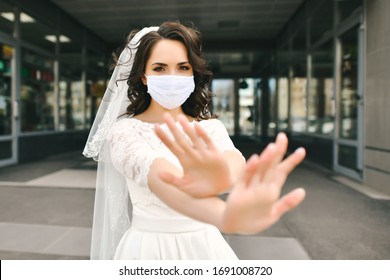 """Bride in medical mask on street of city during coronavirus epidemic.  Clean hands show """"stop"""" and """"no risk"""" gesture. Wedding day COVID-19 protection."""