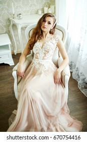 Bride model of a caucasian brunette with long hair, bright make-up in a wedding pink dress with lace in a hotel room next to a mirror, padded stool and window sits in a white armchair