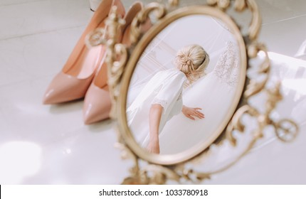bride in the morning dresses touches a wedding dress in the reflection of a desk mirror