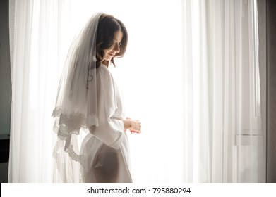 Bride morning preparation. Beautiful bride in white wedding negligee and veil on the background of large bedroom window