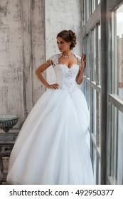 Bride near the window. Wedding Dress. Beautiful bride in a luxury hotel. Wedding in Paris.