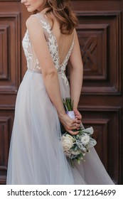 the bride on the background of a wooden door holds a bouquet of roses behind her.  gray backless dress with lace accents