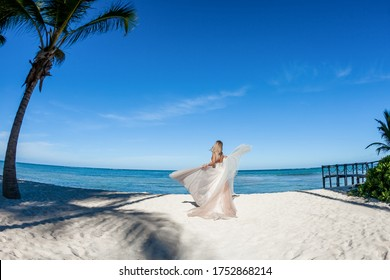 Bride on the beach back view in a white wedding dress walking on the white sandy caribbean beach landscape on  sunny day in Dominican republic