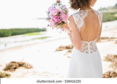 Bride on the coast of the sea, the wind. On the bride is a long wedding dress with lace and an open back.
