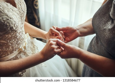 Bride on wedding day holding her mother's hands. Concept of relationship between moms and daughters