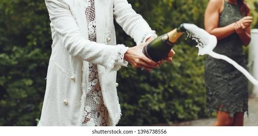 Bride opening a champaigne bottle in a garden.