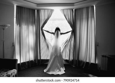 Bride opens curtains standing before bright window. Morning Bride Opens a window view. Black and white photo