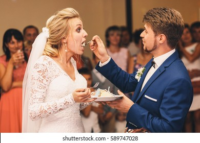 Bride opens her mouth broad tasting wedding cake from groom's fork