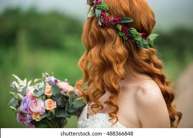 Bride in the park. Red-haired woman. The hair of the girl wreath of flowers.