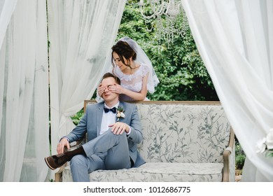 The bride in a pink dress, the groom in a gray suit. The bride and groom are sitting on a beautiful couch in a gazebo in the garden. White tent. The bride and groom are walking in the forest.