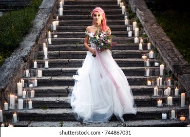 Bride with pink hair and tattoos on her tender shoulder stands on footsteps with shiny candles