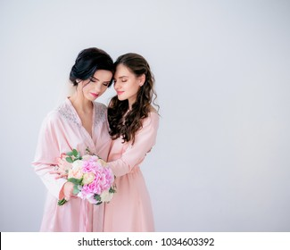 Bride in pink silk robe and her pretty bridesmaid in pink dress hug eac other tender standing in the room