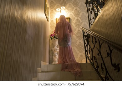 Bride in pink wedding dress walking on stairs in yellowish tungsten light