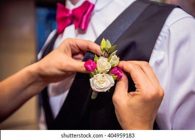 bride pinning boutonierre to groom's suit
