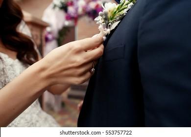 Bride pins beige boutonniere to groom's blue jacket