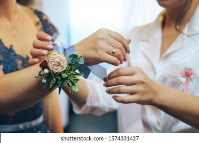 Bride places a flower corsage on the hand of her maid of honour