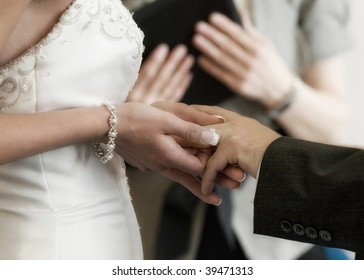 A bride placing a ring on her groom's hand as they get married