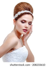 Bride. Portrait of a beautiful woman in wedding white dress, hand touching face. Updo.