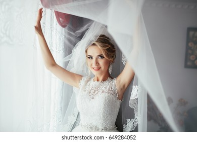 Bride poses under the curtain in bright room