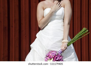 Bride posing against red wall with  wedding bouquet.