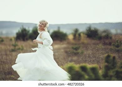 Bride posing on  field. Portrait of a  blonde girl in a wedding dress on the field