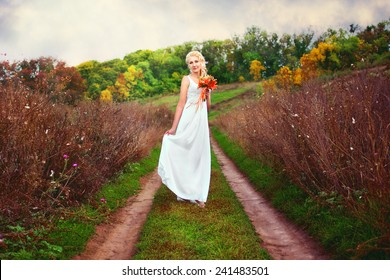 Bride posing outdoors with a bouquet