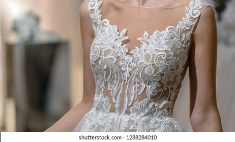 Bride preparing for wedding and wearing dress decorated with lace