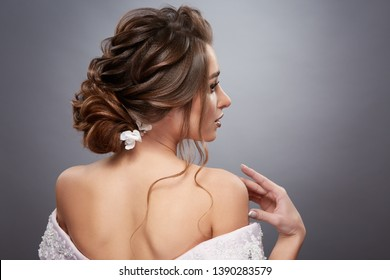 bride with pretty hairstyle touching her shoulder and looking sideways