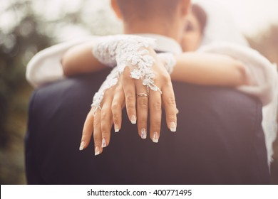 The bride put her hands on the shoulders of the groom. They are kissing. The focus on foreground - on bride's hands. Wedding ring is on bride's hand. The wife embraced her new husband in the sunlight.