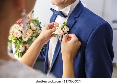 bride puts groom on boutonniere from white roses on wedding day