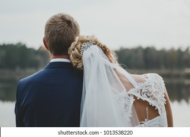 Bride puts her head on groom's shoulder. Tulle bridal veil and white lace dress with scooped back. Romantic elegant photo.
