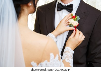 the bride puts on the bridal boutonniere to the groom on the jacket